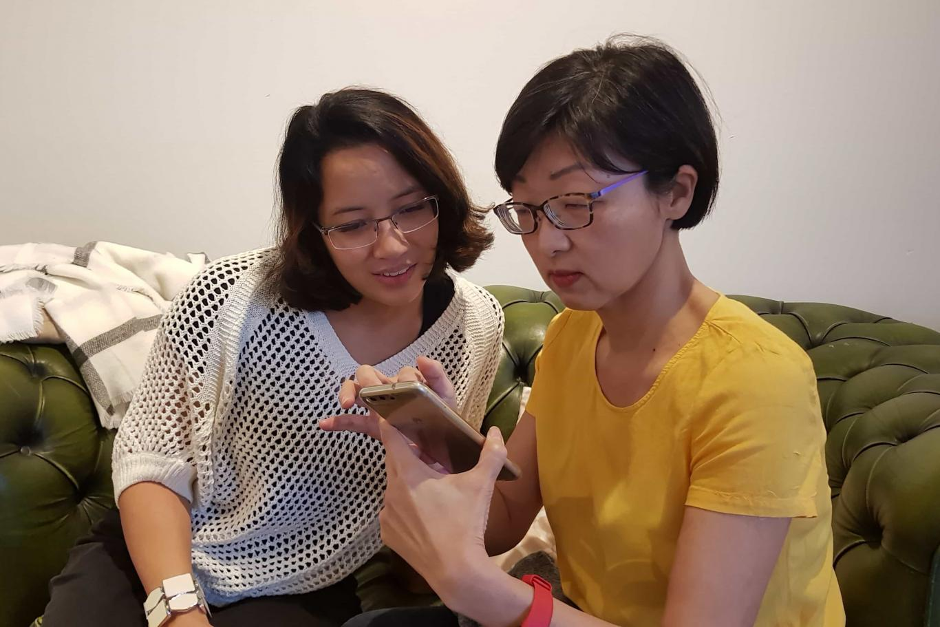 Image of two Asian ladies looking at the phone screen while sitting on the coach